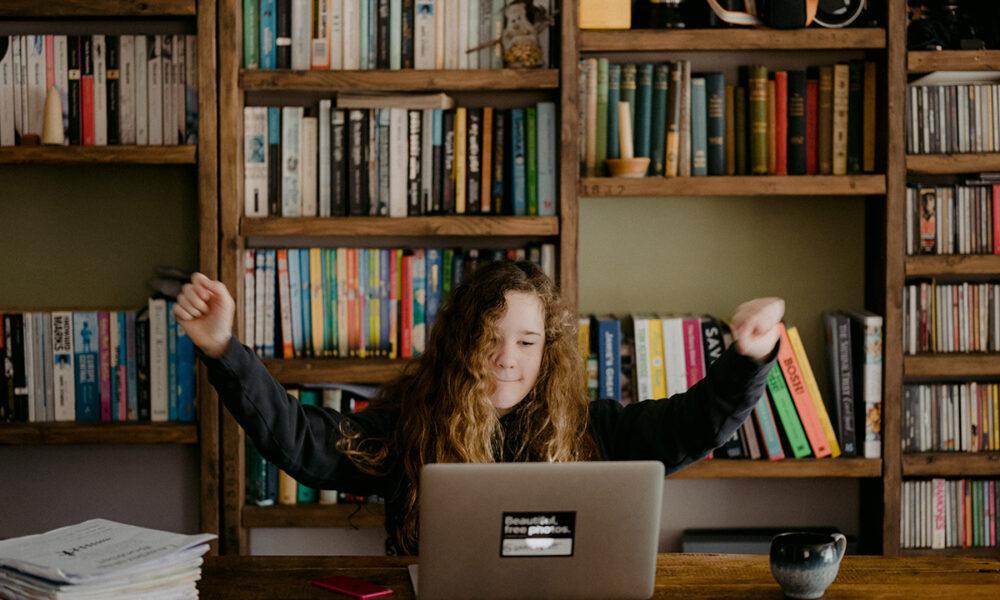 Happy girl behind computer: Annie Spratt