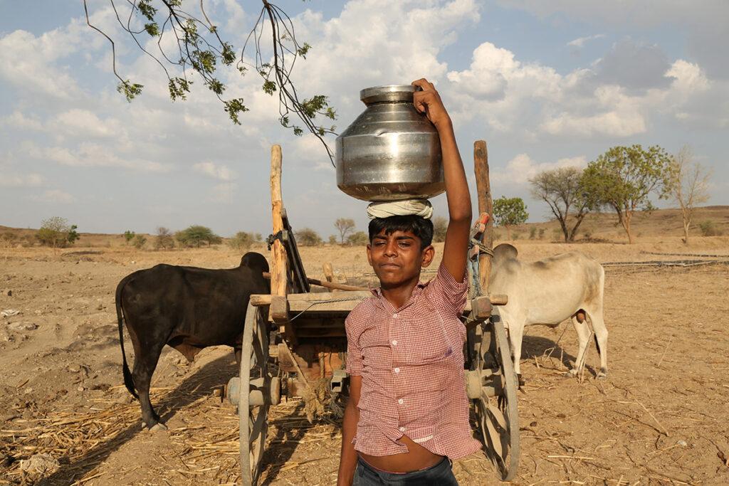 Indiase jongen vervoert drinkwater op hoofd
